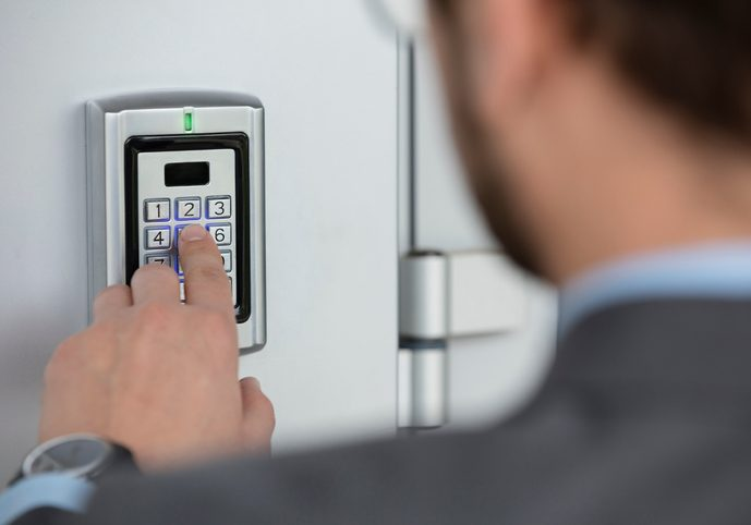 Human hand pressing the security code combination to unlock the door